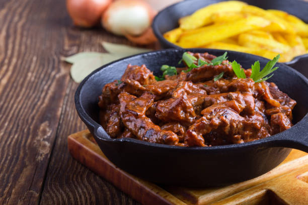 Beef Stroganoff with tomato sauce and sour cream Beef Stroganoff with tomato sauce and sour cream and fried potato served in cast iron skillet on rustic wooden table beef bourguignon stock pictures, royalty-free photos & images