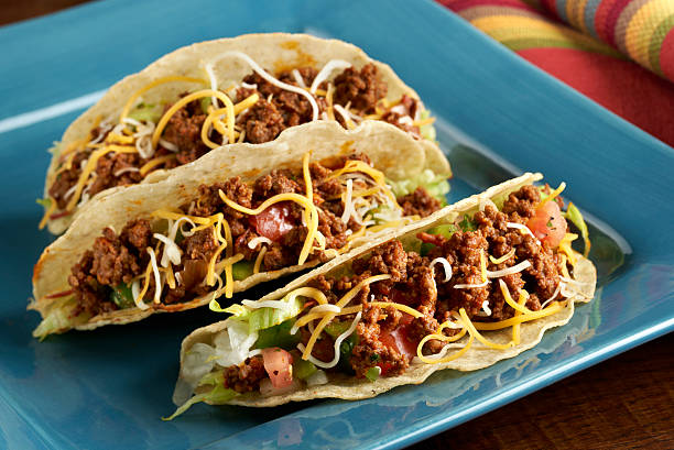 Beef Taco in Hard Shell Three Ground Beef Tacos in crispy corn tortilla shells with lettuce, cheese and tomatoes. Shallow depth of fileld focus on front taco. burwellphotography stock pictures, royalty-free photos & images