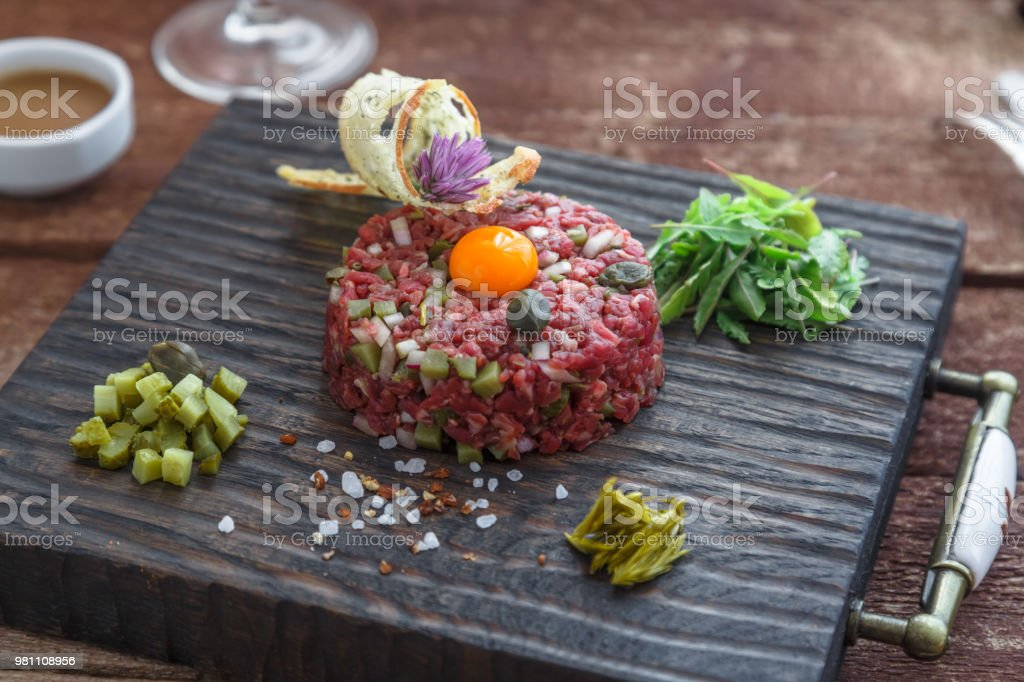 Beef tartare with capers, pickled cucumber and fresh onions on dark background stock photo
