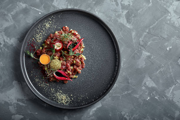 Beef tartare with egg yolk on a gray surface, top view, close-up copy space stock photo