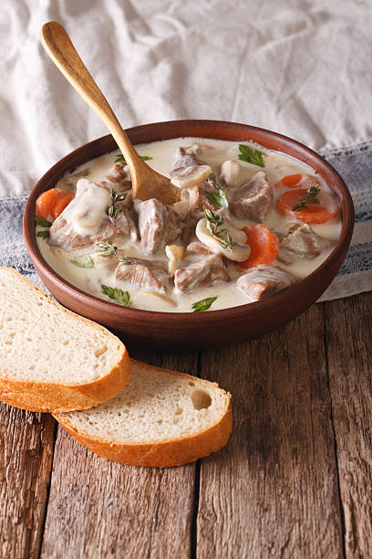 Beef with mushrooms in cream sauce in a bowl. Vertical - Photo