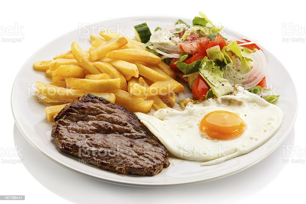 Beefsteak, fried egg, French fries and vegetables stock photo