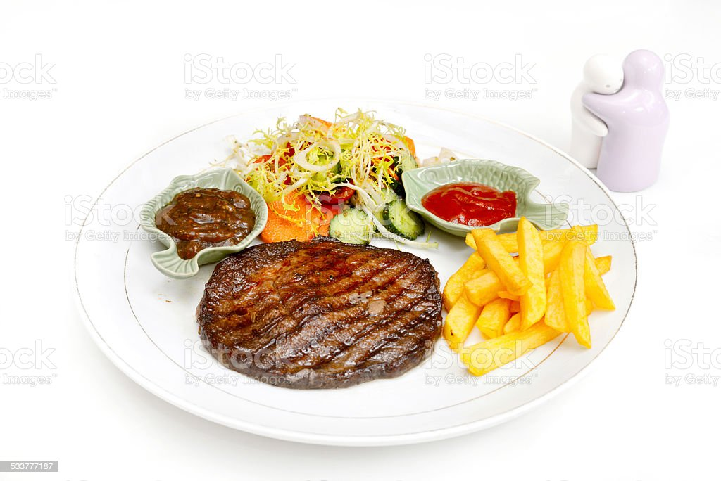 Beefsteak served with fries and salad stock photo