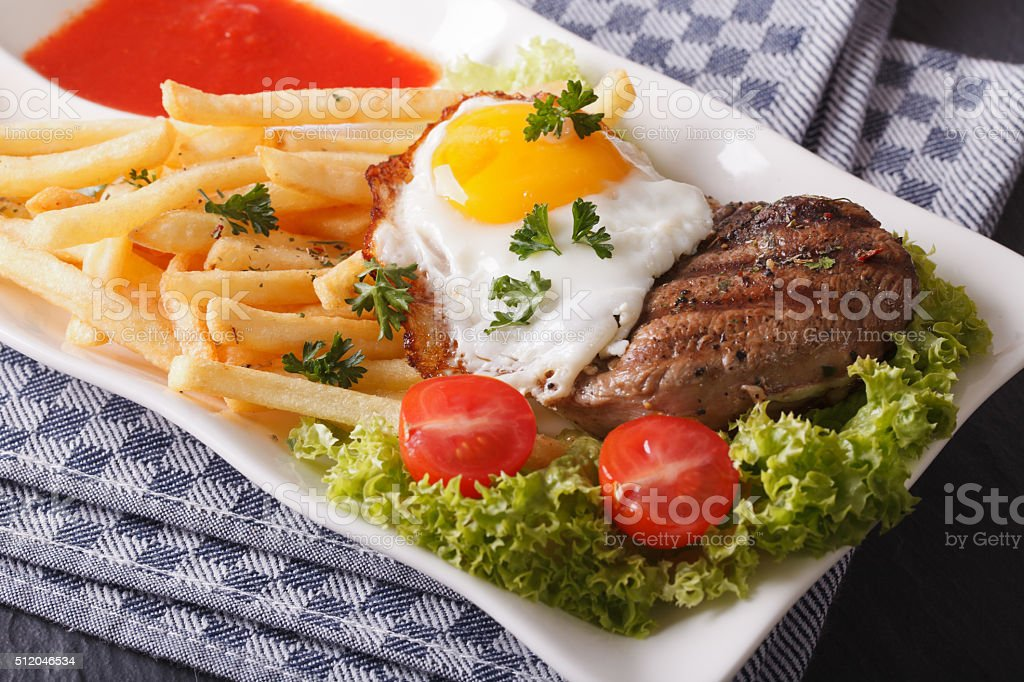 beefsteak with fried egg and fries on a plate closeup stock photo
