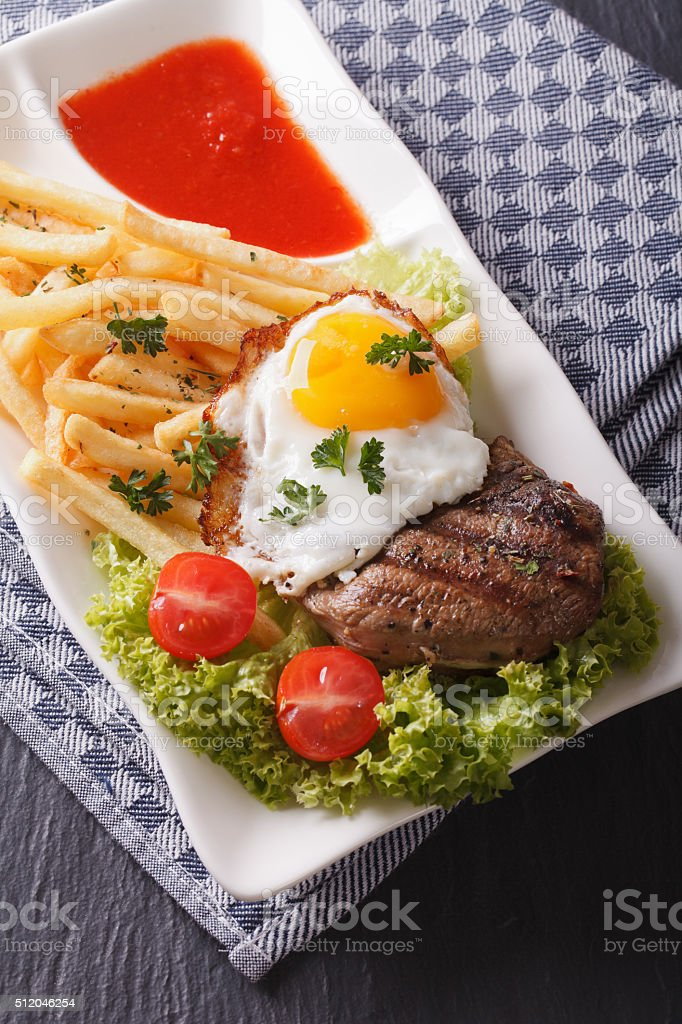 beefsteak with fried egg and fries served on a plate stock photo