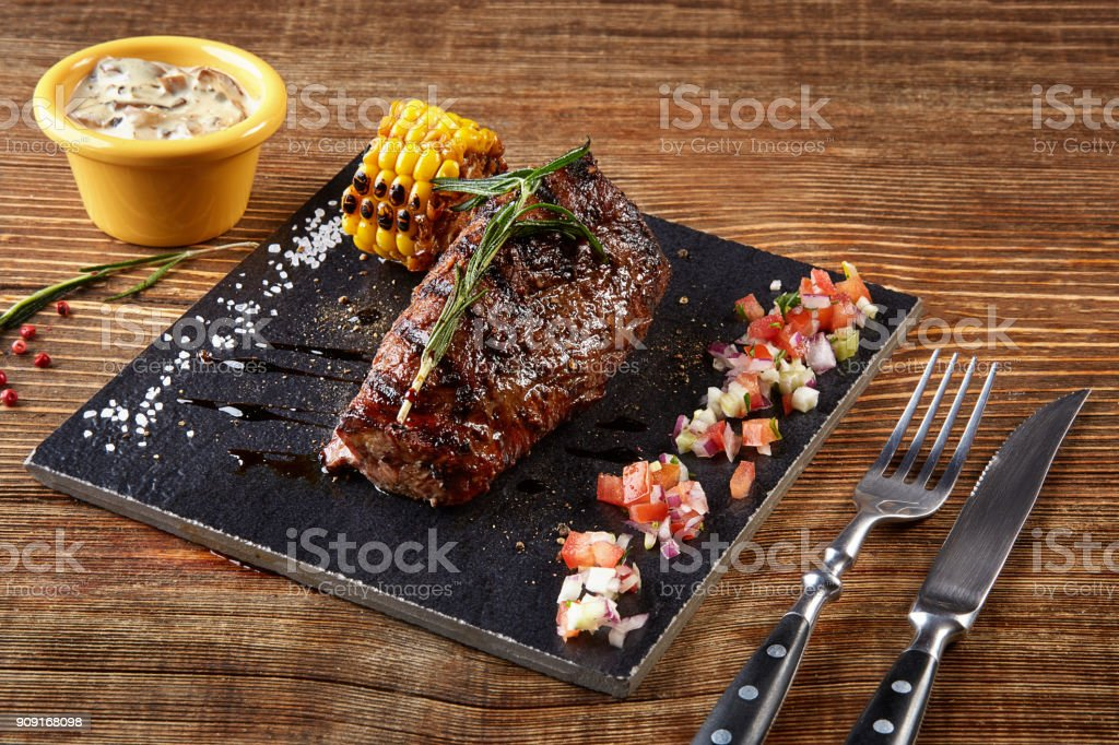 Beefsteak with grilled corn on black board and mushrooms sauce on wooden table stock photo