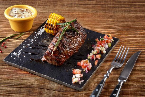 beefsteak mit gegrilltem mais am schwarzen brett und champignons sauce auf holztisch - porzellan schmuck stock-fotos und bilder