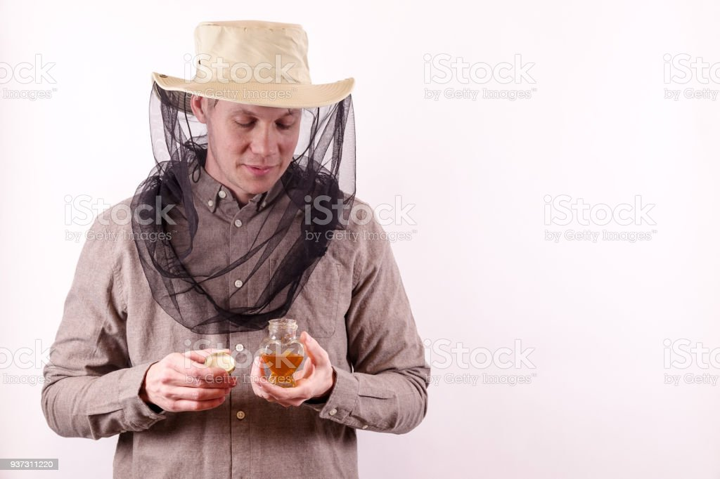 A beekeeper holds a jar of honey stock photo