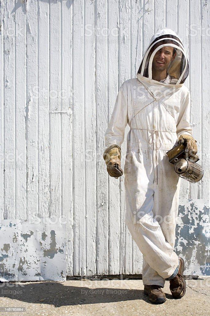 Beekeeper standing in front of a white barn door stock photo