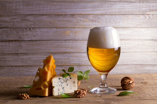 istock Beer and cheese. Glass of beer with cheese, nuts and basil on wooden background 936769876