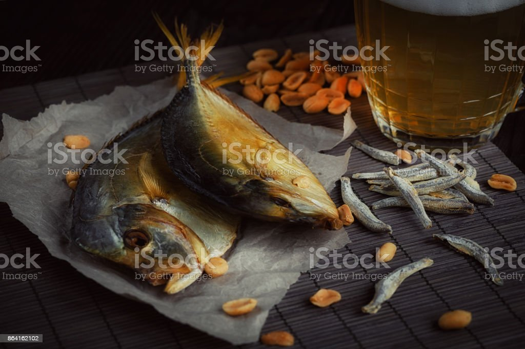 Beer and dried fish on dark wooden table. royalty-free stock photo
