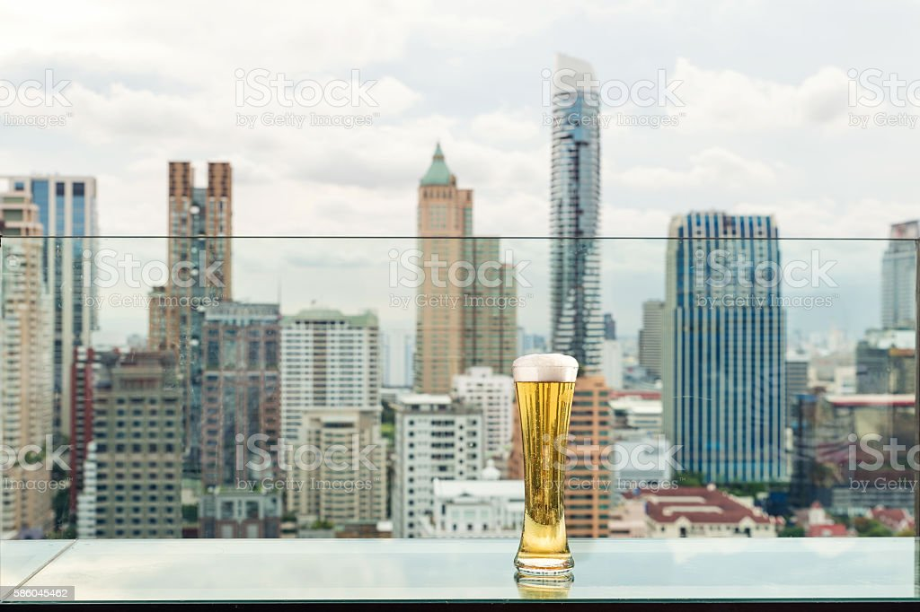Beer and foam beer on table in rooftop bar. - foto stock