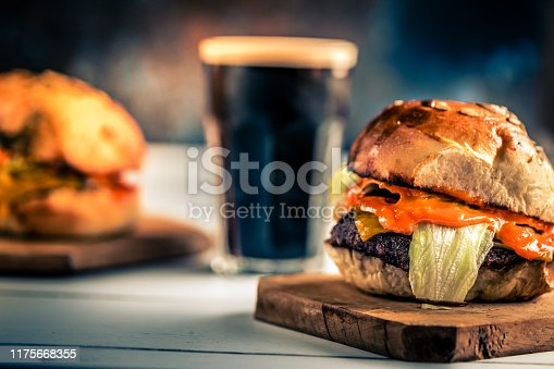 Close up color image depicting a glass of cold beer (dark stout beer, with a white foam head) with fresh flame grilled burgers presented on wooden boards on top of a white wooden surface. The beef burgers are sandwiched between fresh glazed seeded buns, on a bet of green lettuce leaves and stuffed with melted cheese. Room for copy space.