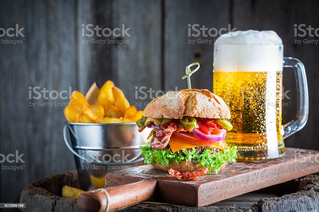 Beer and fresh hamburger made of beef, cheese and vegetables - foto de acervo