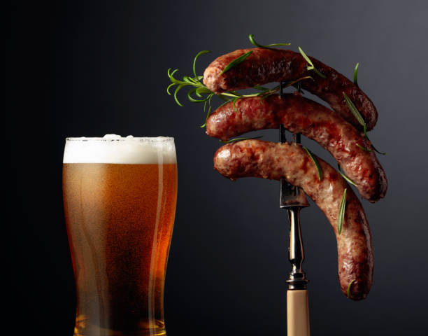Beer and grilled Bavarian sausages with rosemary. Sausages on a fork sprinkled with rosemary. stock photo