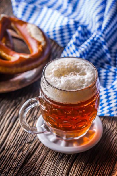 bier und oktoberfest. entwurf der bier brezel und blau karierte tischdecke als traditionelle produkte für bayerische festival oktoberfest - bayerische brotzeit stock-fotos und bilder