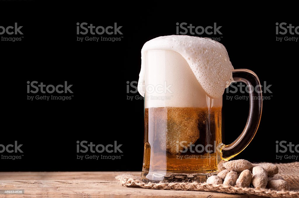 beer and peanuts on wooden table stock photo