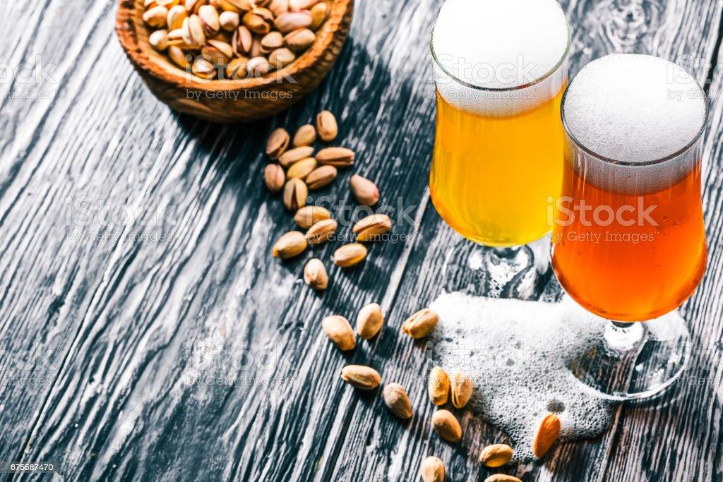 Bière et pistache sur bois noir photo libre de droits