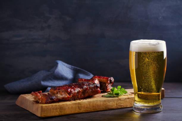 Cerveza y costillas de cerdo. Cerveza y carne. El concepto de cerveza y comida - foto de stock