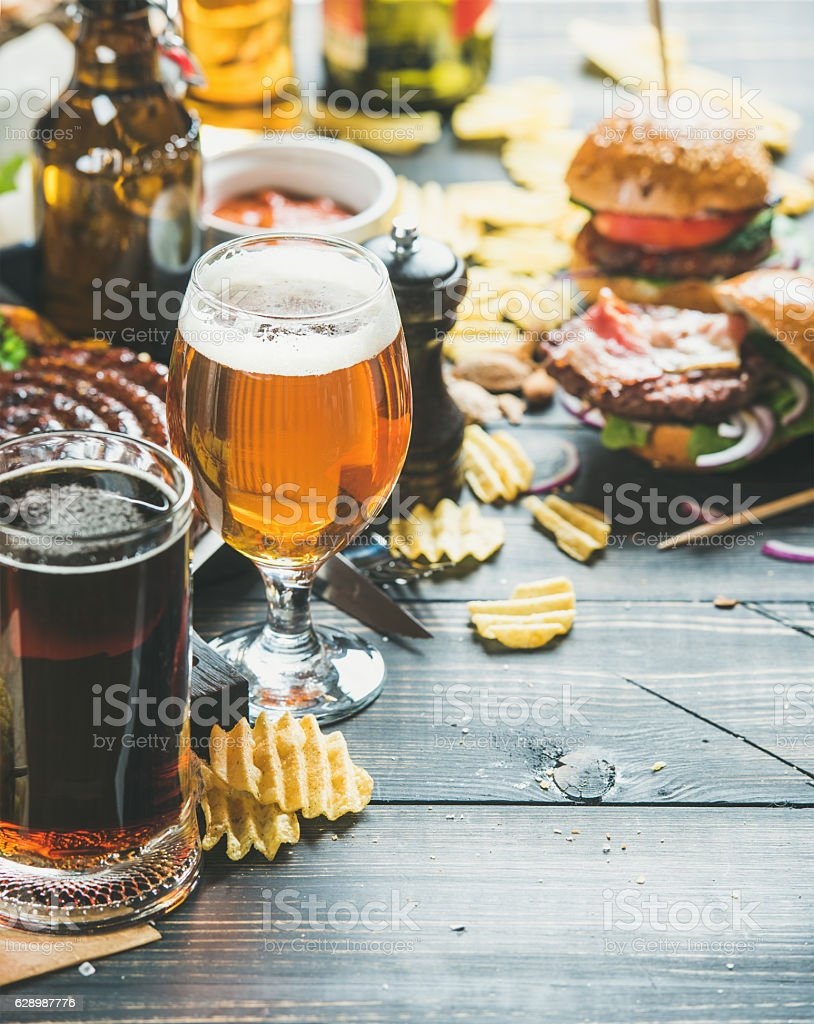 Beer and snack variety on dark wooden scorched background stock photo