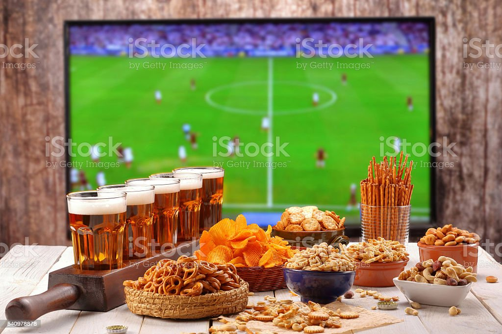Beer and snacks set on football match tv background - foto de acervo