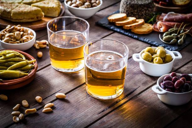 bier und tapas am rustikalen holztisch erschossen - tapas stock-fotos und bilder