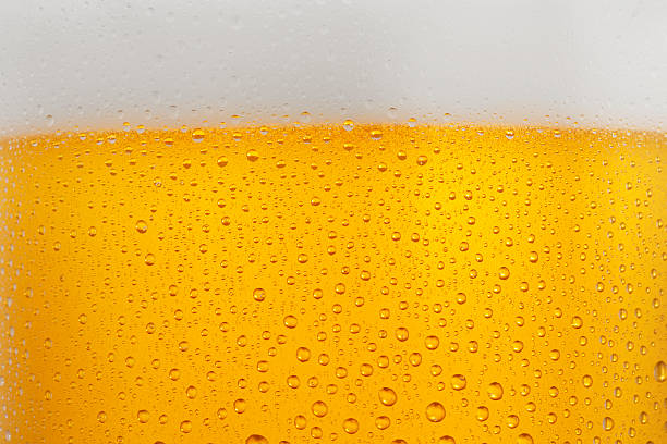 Beer Background   Ice Cold  Glass Covered with water drops  condensation Beer Background. Close up drops of a Ice Cold Glass of Beer, covered with water drops - condensation.  pilsner stock pictures, royalty-free photos & images