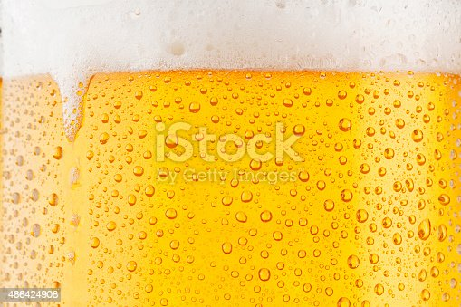 Close up drops of a Ice Cold Pint of Beer, covered with water drops - condensation. The background is clear with the emphasis on water drops on yellow-golden background.