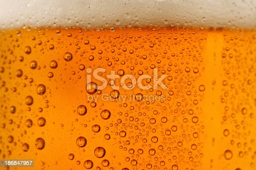 Close up drops of a Ice Cold Pint of Beer- condensation. The background is clear with the emphasis on water drops on yellow-golden background.SEE ALSO: