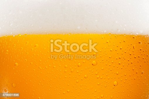 Close up drops of a Ice Cold Pint of Beer,  with condensation. The background is clear with the emphasis on water drops on yellow-golden background.
