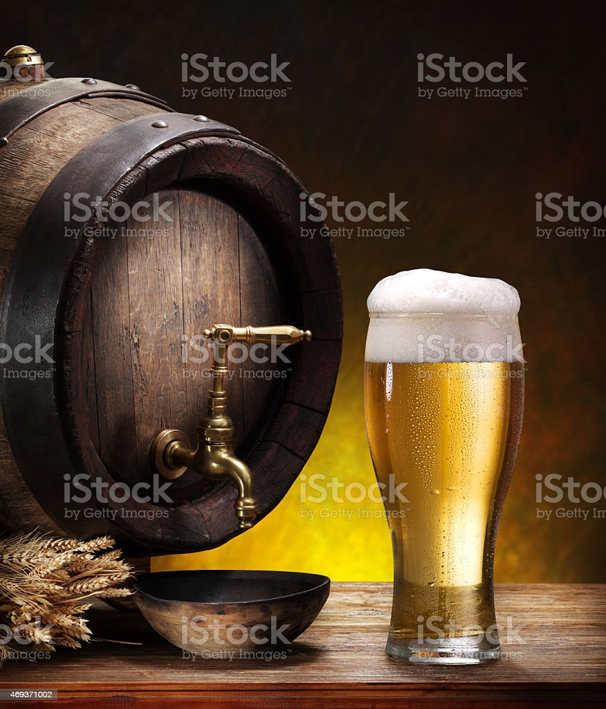 Beer barrel with a glass pint of beer on wood table stock photo