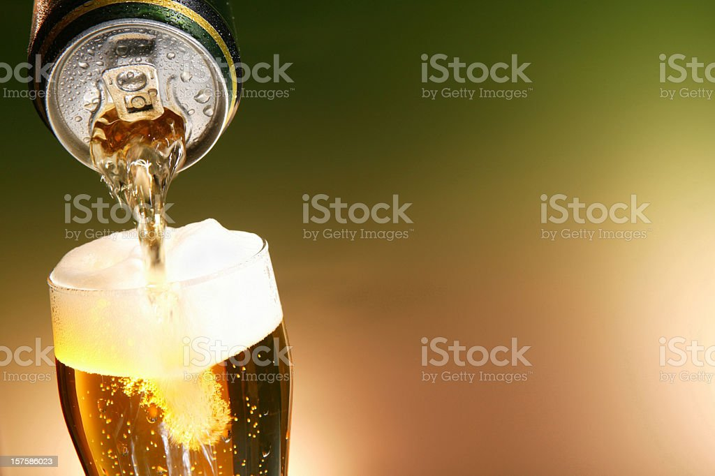 Beer being poured from a can into a glass stock photo