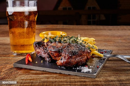 istock Beer being poured into glass with gourmet steak and french fries on wooden background 904426858