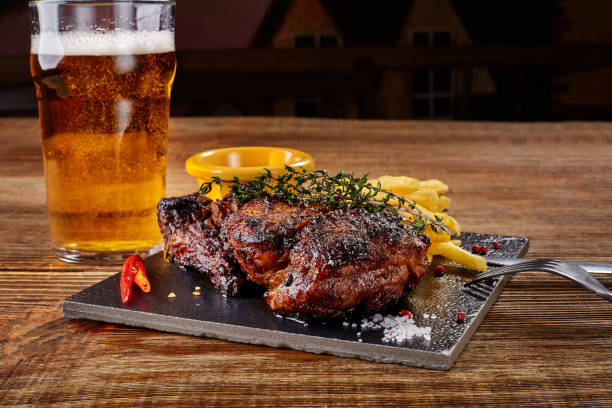 Beer being poured into glass with gourmet steak and french fries on wooden background stock photo