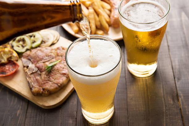 Cerveza siendo vertido en un vaso con bistec y patatas fritas - foto de stock