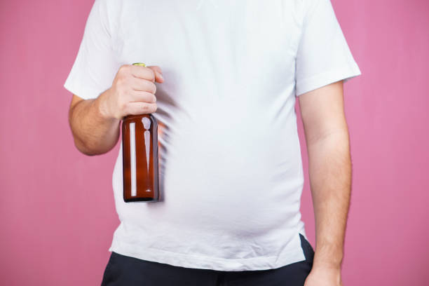 beer belly, alcoholic addiction. fat man with beer stock photo