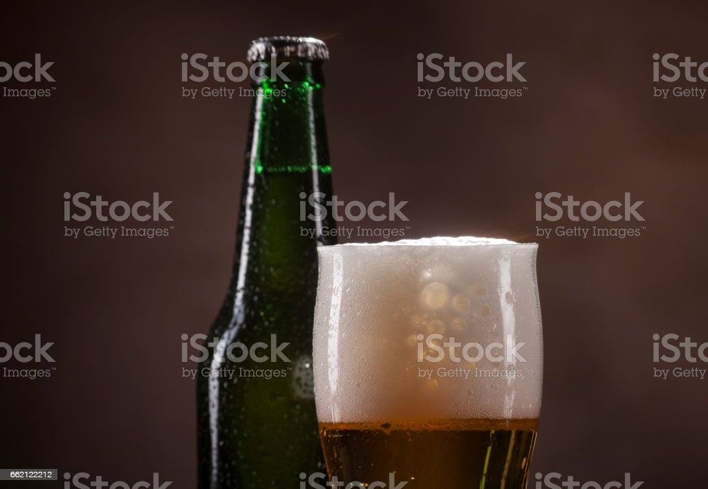 Beer bottle and mug on brown background royalty-free stock photo