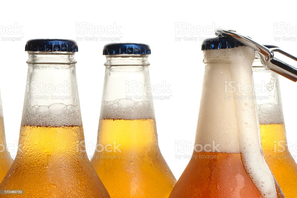 Beer bottle being opened with froth stock photo
