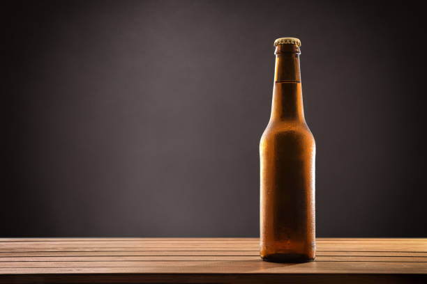 Beer bottle filled and closed on wood table black background. stock photo