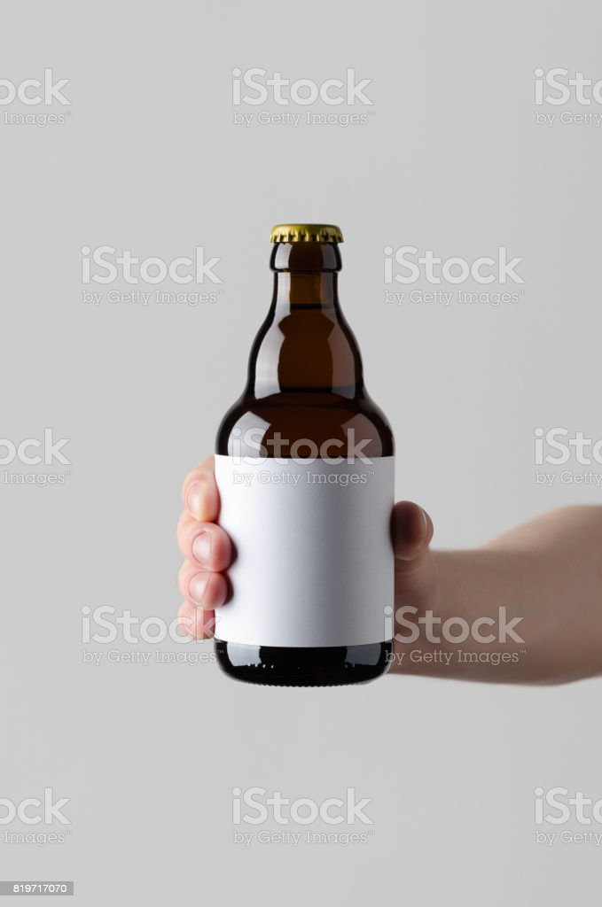 Beer Bottle Mock-Up. Blank Label - Male hands holding a beer bottle on a gray background stock photo