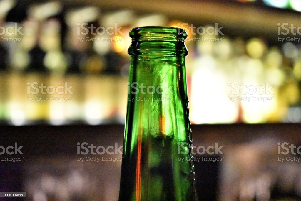 A partial of a green beer bottle with a blurred bar in the background