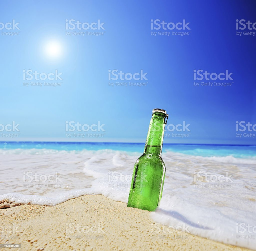 Beer bottle on a sandy beach with clear sky stock photo