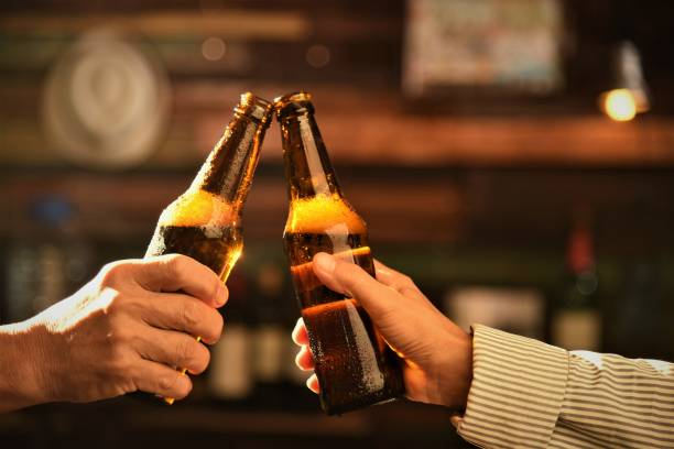 beer bottle friends toasting beer bottles celebratory toast stock pictures, royalty-free photos & images