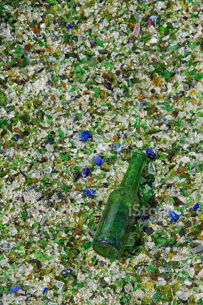 Beer bottle that escaped the crusher in a recycling plant stock photo