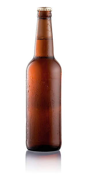 beer bottle with condensation water drops isolated on white background - dark beer stock photos and pictures