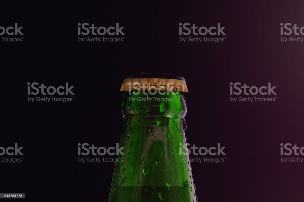 Beer Bottle with Droplet in the Dark Light stock photo
