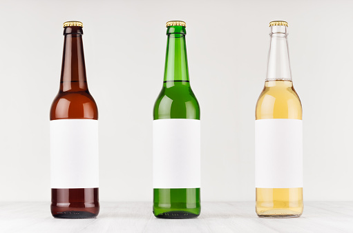 Beer bottles 500ml - brown, green, transparent with blank white label on white wooden board, mock up.