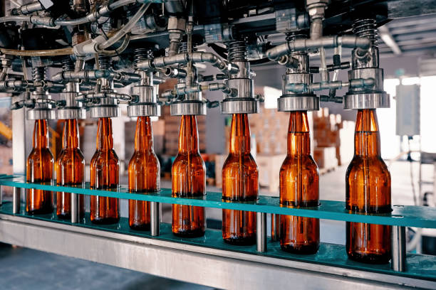 пивные бутылки, наполненные конвейерной лентой на пивоваренном заводе - напиток стоковые фото и изображения