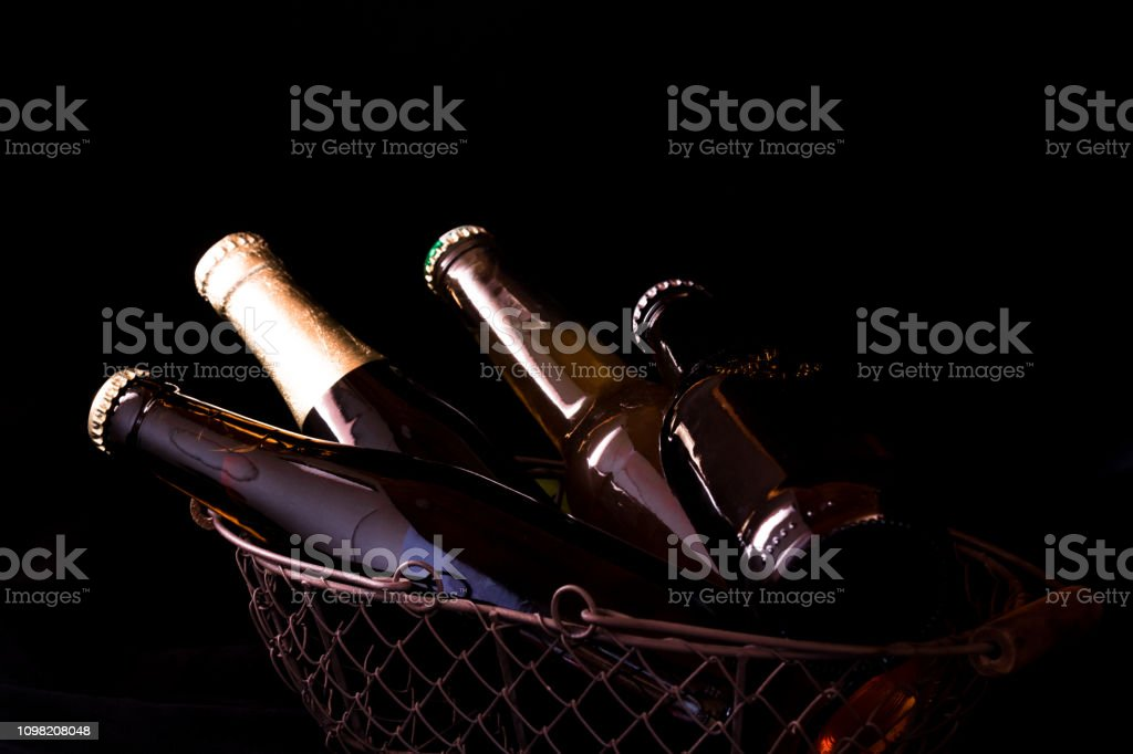 beer bottles on a black background chiaroscuro in an old metal mesh...