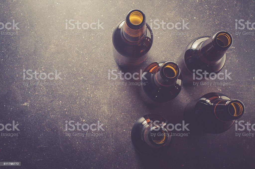 Beer bottles on dark table​​​ foto